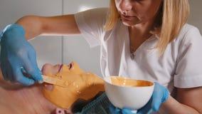 Ung kvinnlig ansiktsbehandling för maskering för passerandebehandlingfrukt på brunnsortsalongen stock video