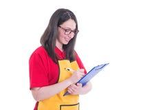 Ung kvinnlig anställd som gör inventarium i lagret fotografering för bildbyråer
