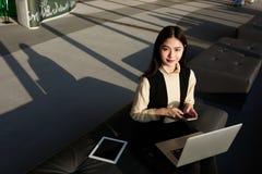 Ung kvinnlig användande bärbar dator och smartphone royaltyfria foton