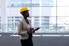 Ung kvinnlig arkitekt för afrikansk amerikan med digitalt minnestavlaanseende i modernt kontor royaltyfria bilder