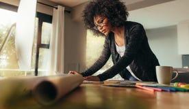 Ung kvinnlig arkitekt som hemifrån arbetar på ett kontor för projekt arkivbild
