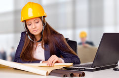 Ung kvinnlig arkitekt som studerar plan Royaltyfria Foton