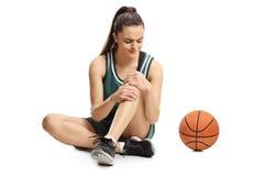 Ung kvinnlig basketspelare som sitter på ett golv och rymmer hennes smärtsamma knä royaltyfria bilder
