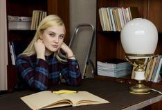 Ung kvinnlig bibliotekarie som läser en stor bok i arkiv bokhyllor med böcker, trappstegen och skrivbordet med lampan arkivbild