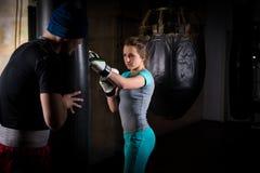 Ung kvinnlig boxare i boxninghandskar som utbildar med hennes soffa och Royaltyfri Fotografi