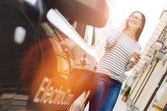Ung kvinnlig chaufför som talar på telefonen nära bilen Fotografering för Bildbyråer