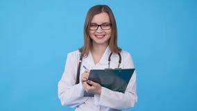 Ung kvinnlig doktor i det vita laget med skrivplattan lager videofilmer