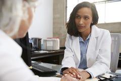Ung kvinnlig doktor i konsultation med den höga patienten royaltyfri bild