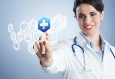 Ung kvinnlig doktor som använder pekskärmmanöverenheten. Fotografering för Bildbyråer