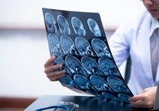 Ung kvinnlig doktor som rymmer MRI- eller CT-bildläsningsbild royaltyfri bild