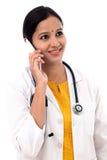 Ung kvinnlig doktor som talar på mobiltelefonen Fotografering för Bildbyråer