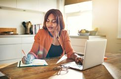 Ung kvinnlig entreprenör som arbetar på en bärbar dator i hennes kök royaltyfria bilder