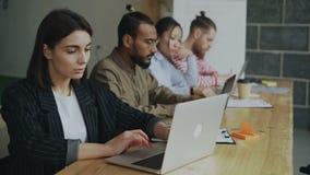 Ung kvinnlig entreprenörfreelancer som arbetar och använder bärbar datordatoren på det upptagna coworking kontoret Affärskvinna o lager videofilmer