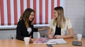 Ung kvinnlig formgivare som talar till hennes klient som ler med tabellen som är full av legitimationshandlingar, prövkopior och  stock video