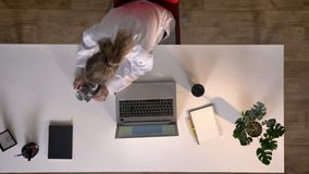 Ung kvinnlig forskare i det vita laget som ser i mikroskop och skriver på bärbara datorn, topshot, medicinskt laboratorium stock video