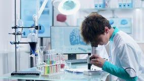 Ung kvinnlig forskare i medicinsk kl?der som arbetar i modernt laboratorium arkivfilmer