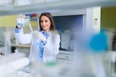 Ung kvinnlig forskare som för laboratoriumprovet arkivbilder