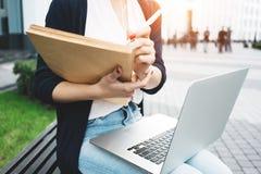Ung kvinnlig forskning för freelancerdanandearbetsmarknad på den moderna bärbara datorn, sitter på det fria i stads- gata arkivbilder