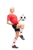 Ung kvinnlig fotbollspelare som jonglerar en boll arkivbild