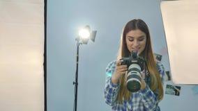 Ung kvinnlig fotograf med kameran i professionellt utrustad studio lager videofilmer