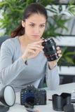 Ung kvinnlig fotograf som kontrollerar den digitala kameran Royaltyfri Foto