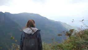 Ung kvinnlig fotvandrare med ryggsäcken som når upp överkant av berget och lyftta händer Kvinnaturist i regnrockanseende på arkivfilmer