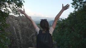 Ung kvinnlig fotvandrare med ryggsäcken som når upp överkant av berget och lyftta händer Turist- anseende för kvinna på kanten av stock video