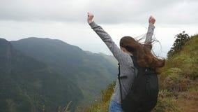 Ung kvinnlig fotvandrare med ryggsäcken som når upp överkant av berget och lyftta händer Turist- anseende för kvinna på kanten av arkivfilmer