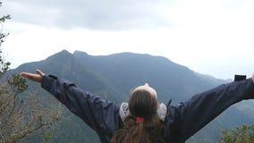 Ung kvinnlig fotvandrare med ryggsäcken som når upp överkant av berget och lyftta händer Turist- anseende för kvinna på kanten av lager videofilmer