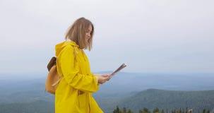 Ung kvinnlig fotvandrare som ser översikten från bergöverkant lager videofilmer