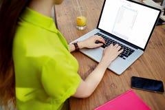 Ung kvinnlig freelancerflicka som arbetar på netbook under frukosten i modern hipstercoffee shop Fotografering för Bildbyråer