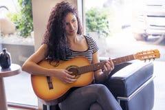 Ung kvinnlig gitarrist som hemma spelar på soffan royaltyfri foto