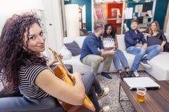 Ung kvinnlig gitarrist som hemma spelar på soffan royaltyfri bild