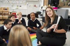 Ung kvinnlig grundskola för barn mellan 5 och 11 årlärare som läser en bok till barn som sitter på golvet i ett klassrum, selekti arkivfoto