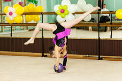 Ung kvinnlig gymnast som gör sluga splittringar på konstgymnastik Fotografering för Bildbyråer
