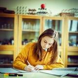 Ung kvinnlig högskolestudent i kemigrupp som skriver anmärkningar Fokuserad student i klassrum royaltyfria foton