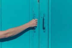 Ung kvinnlig hand som griper den blåa dörren royaltyfria foton