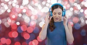 Ung kvinnlig hipster som lyssnar till musik på hörlurar mot bokeh royaltyfri bild