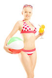 Ung kvinnlig i bikinin som rymmer en strandboll och coctail Arkivfoto