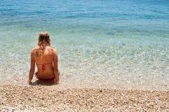 Ung kvinnlig i bikinisammanträde i det grunda havet som lämnas Arkivfoton