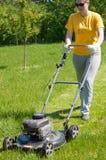 Ung kvinnlig i gården - driftig gräsbrämgräsklippare Royaltyfri Foto