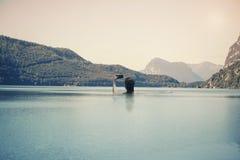 Ung kvinnlig i vattnet på sjön på bakgrunden av italienska berg i södra Tirol Arkivfoto