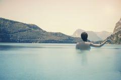 Ung kvinnlig i vattnet på sjön på bakgrunden av italienska berg i södra Tirol Royaltyfria Foton