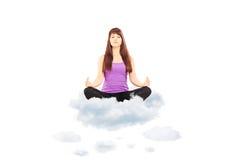 Ung kvinnlig idrottsman nen i dräktsammanträde på moln och att meditera Royaltyfri Foto