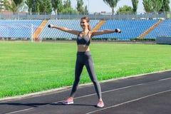 Ung kvinnlig idrottsman nen med hantlar som sträcker och värmer upp på kört spår i stadionsport och konditionbegrepp royaltyfria bilder