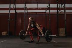 Ung kvinnlig idrottsman nen som gör deadliftövning Stark kvinna som lyfter den tunga skivstången på crossfitidrottshallen royaltyfri bild