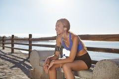 Ung kvinnlig jogger som vilar på kustlinjen Royaltyfria Bilder