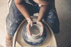 Ung kvinnlig keramiker som arbetar på ett hjul för keramiker` s Arkivbild