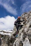 Ung kvinnlig klättrare på ett brant via Ferrata i den södra Tyrolen arkivfoto