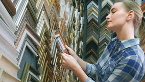 Ung kvinnlig klient som söker efter en ram i specialt lager Arkivbilder